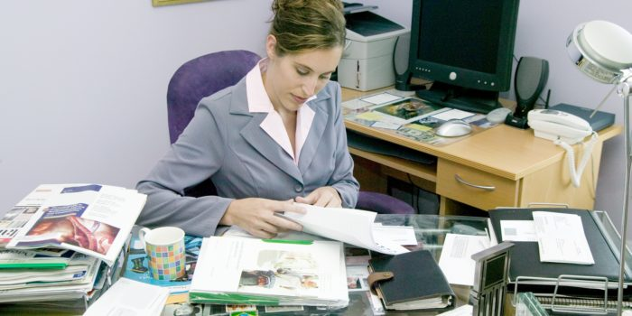 A Young Woman In A Business Suit Busy Working In Her Office